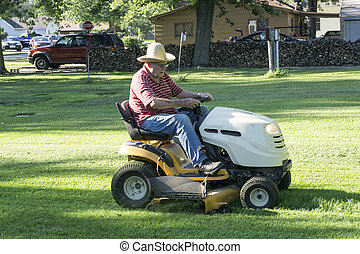 Older Gentleman Cutting His Grass While Wearing A Straw Hat