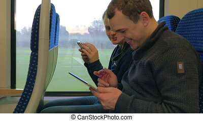 Friends with Gadgets on Train - Man and woman are sitting in...