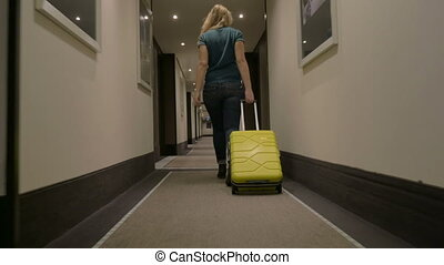 Woman Walking along the Hotel Passage with Trolley Bag -...