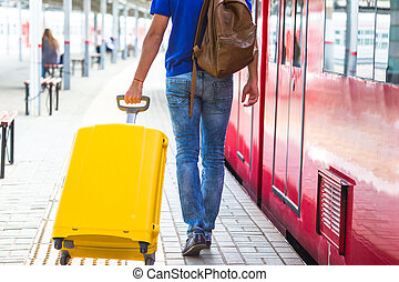 Back view of man with luggage at a train station - Young man...