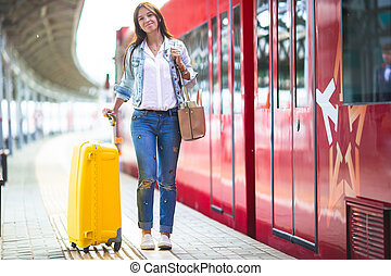 Young woman with luggage at a train station waiting for...