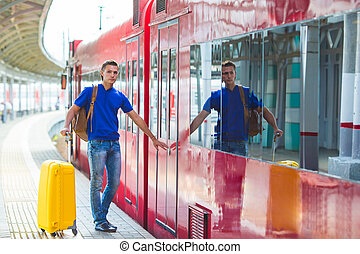 Young man with baggage at a train station near Aeroexpress -...
