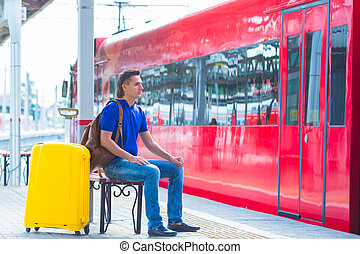 Young man with luggage at a train station waiting for...