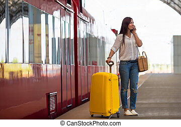 Young woman with luggage talking by cellphone at a train...