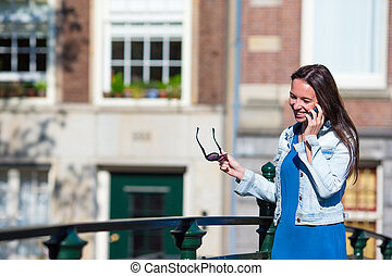 Young happy girl talking by cell phone in european city -...