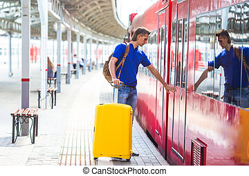 Young man with baggage at a train station near express train...