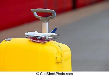 Red passports and airplane small model on yellow luggage at...