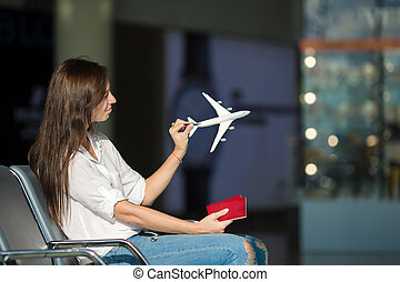 Pretty young female passenger with small model airplane at...