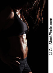 Muscular young woman posing in sportswear - Cropped image of...