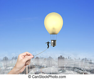 Businessman walking tightrope woman hand pulling lightbulb hot air balloon