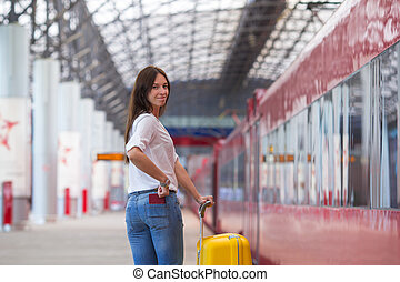Young happy woman with yellow luggage at a train station -...