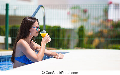 Young beautiful woman listening music with headphones near swimming pool