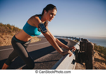 Young female athlete leaning on guardrail - Young female...