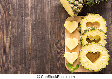Pineapple slices with a cut in the shape of hearts on wooden background