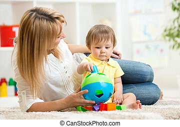 Baby and Mother. Kid boy playing with educational toy.