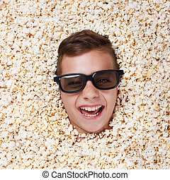 Laughing young boy in stereo glasses looking out of popcorn...