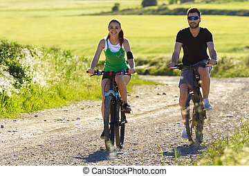 Happy young couple on a bike ride in the countryside -...