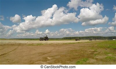 military vehicles driving on a country road in the afternoon