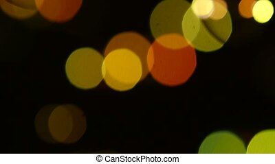 Yellow, green and orange soap bubbles on black, background, bokeh, close up, slow motion