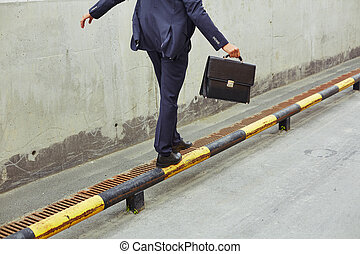 Equilibrium - Rear view of businessman with briefcase...