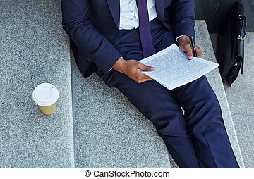 Reading document - Close-up of businessman reading document...