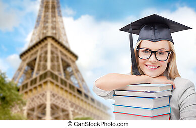 student in trencher with books over eiffel tower -...