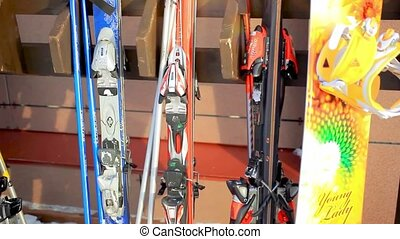 snowboards and skis standing on a wooden rack in a sunny winter day at resort