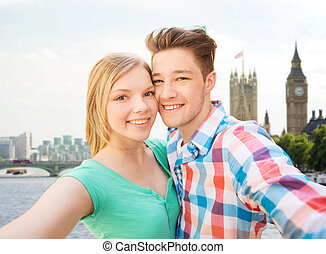 happy couple taking selfie over london city - travel,...