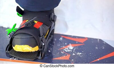 Mens hands are fixed to the board snowboard boots close up...