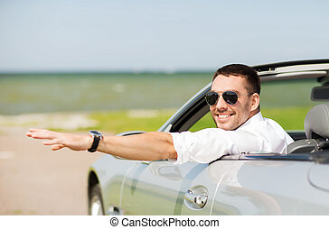 happy man driving cabriolet car and waving hand - auto...