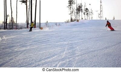Free-rider skiers moving down in snow powder at sunset