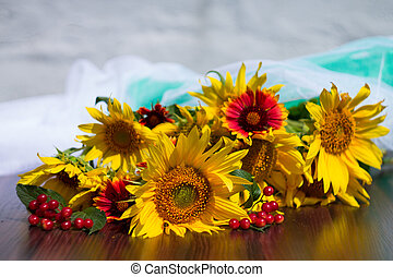sunflowers,  viburnum and red flowers on a blurred background