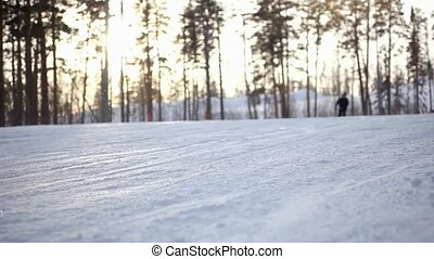 blurred skier ride the mountain at sunset during snowfall -...