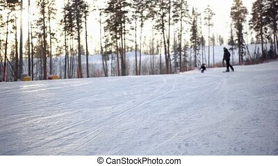 skiers and snowboarder moving down in snow powder at sunset...