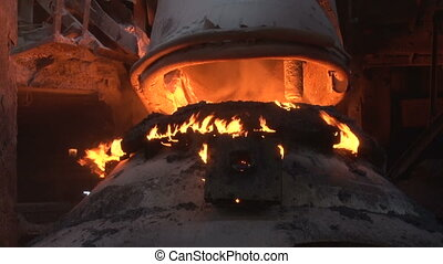 a basic oxygen furnace closeup - pipe is lowered into the...
