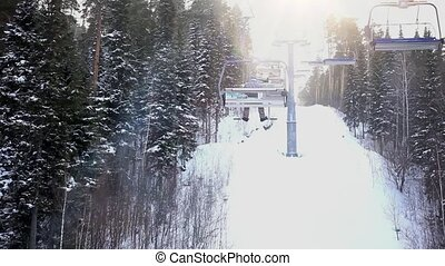 winter ski landscape with pine trees covered with snow and ski lift . during snowfall