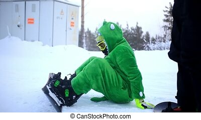 Smiles snowboarder dressed kigurumi on piste slides down the...