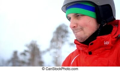 smiles snowboarder wearing a helmet and mittens on the mountain background