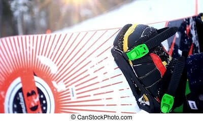 Snowboarder sitting in the mountains during a snowfall . view of his boots and board