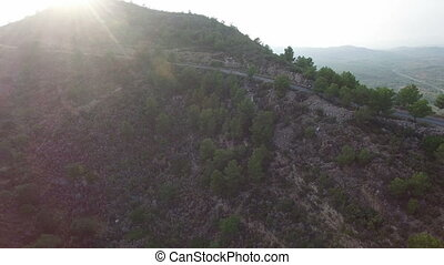 Aerial view of cyclist on high slope mountain road - High...