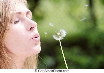 The blonde in park with a dandelion in hands - The blonde...