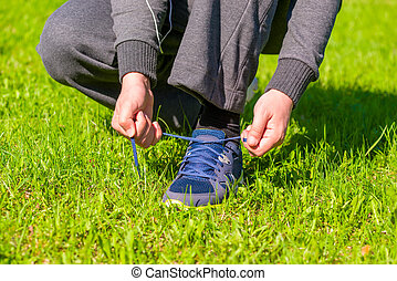 mans hands tying shoelaces from sneaker