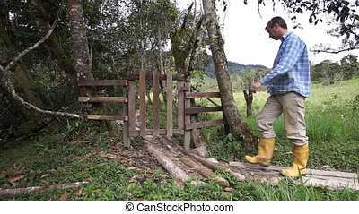 Man in Rubber Boots and a Gate - Man in yellow rubber boots...