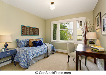 Cozy home office or quest room with blue bed.