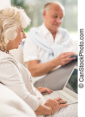 Senior woman using laptop and her husband in background