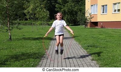 little girl jumping rope outside - little girl in white...