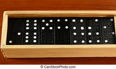Domino game in open and closed box, isolated on wooden...