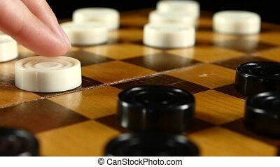 Two persons start playing on checker board, slow motion, close up