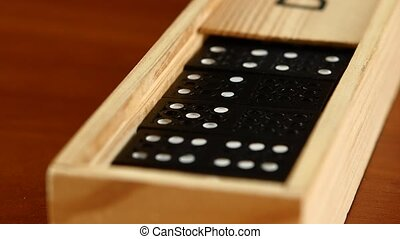 Domino game in closed box, isolated on wooden surface, slow...