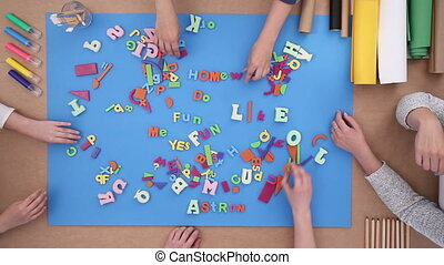 Children building words from color plastic letters